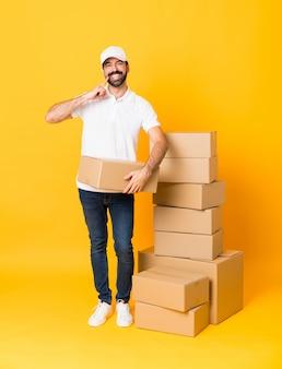 Bezorger onder dozen lachend met een gelukkige en aangename uitdrukking