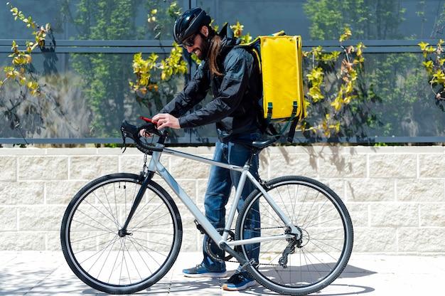 Bezorger op fiets kijkend naar smartphone