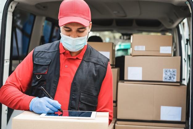 Bezorger schrijft ontvangstbewijs tijdens pandemische tijd van het coronavirus