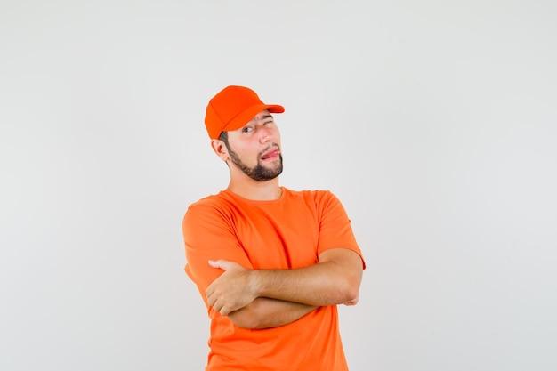 Bezorger staat met gekruiste armen, knipogend oog, tong uitsteekt in oranje t-shirt, pet vooraanzicht.