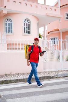 Bezorger steekt de weg over en draagt een gele thermische tas. geconcentreerde kaukasische koerier met tablet in handen die bestelling te voet aflevert.