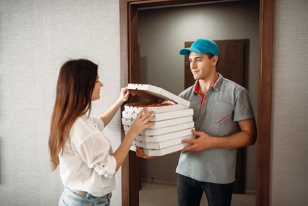 Bezorger toont pizza aan klant bij de deur