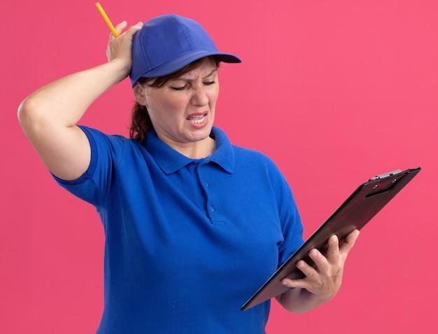 Bezorger van middelbare leeftijd in blauw uniform en pet met klembord en potlood kijken met hand op haar hoofd met teleurgestelde uitdrukking staande over roze muur