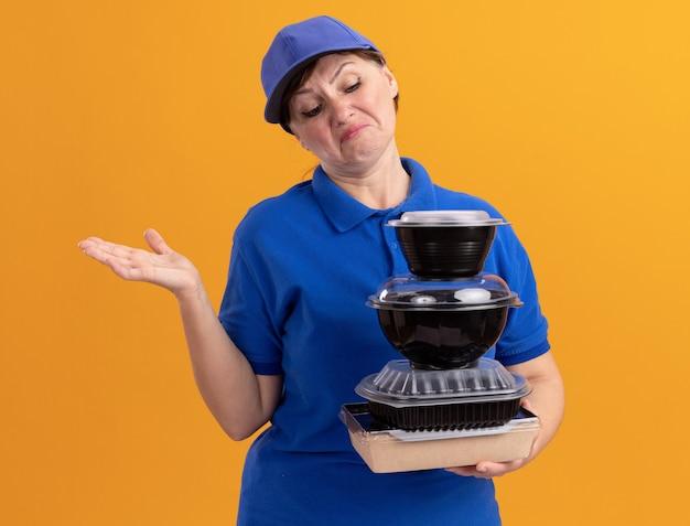 Bezorger van middelbare leeftijd in blauw uniform en pet met stapel voedselpakketten kijkend naar hen verward en ontevreden met opgeheven arm staande over oranje muur