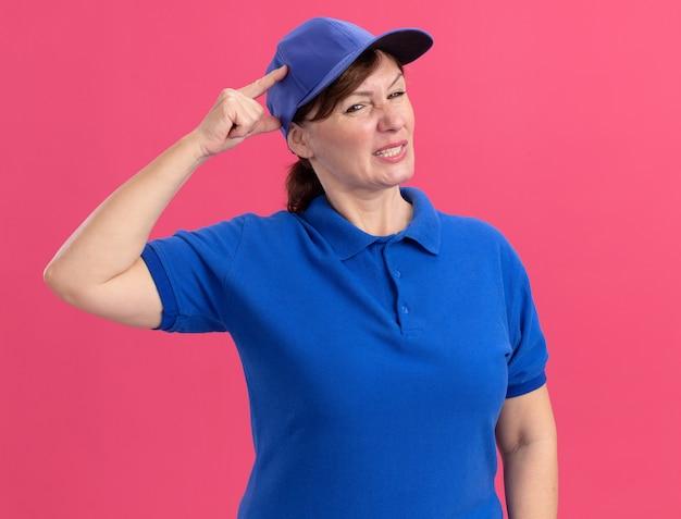 Bezorger van middelbare leeftijd in blauw uniform en pet op zoek verward en erg angstig met hand op haar hoofd staande over roze muur