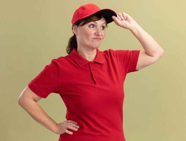 Bezorger van middelbare leeftijd in rood uniform en pet opzij kijken verward en ontevreden haar pet aanraken die zich over groene muur bevindt