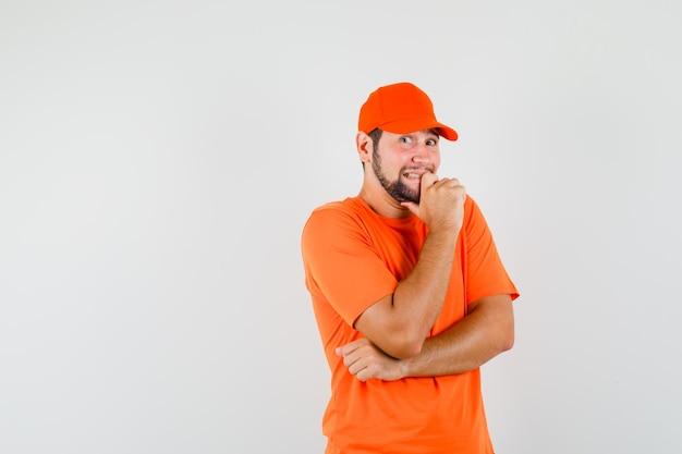 Bezorger voelt zich ongemakkelijk in oranje t-shirt, pet en ziet er opgewonden uit, vooraanzicht.