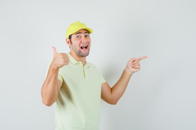 Bezorger wijst opzij, duim opdagen in geel uniform en kijkt gelukkig, vooraanzicht.