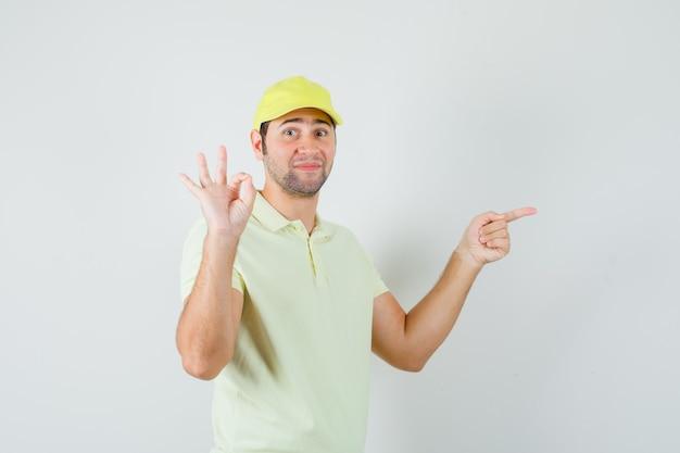 Bezorger wijst opzij, toont ok teken in geel uniform en kijkt zelfverzekerd. vooraanzicht.