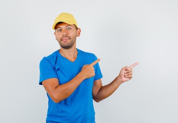 Bezorger wijst weg in blauw t-shirt, pet en ziet er vrolijk uit