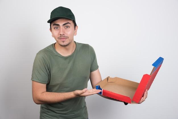 Bezorger wijzend op lege pizzadoos op witte achtergrond.