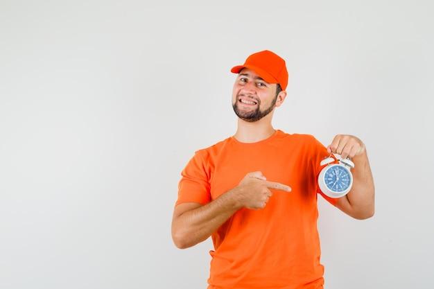 Bezorger wijzend op wekker in oranje t-shirt, pet en vrolijk kijkend. vooraanzicht.