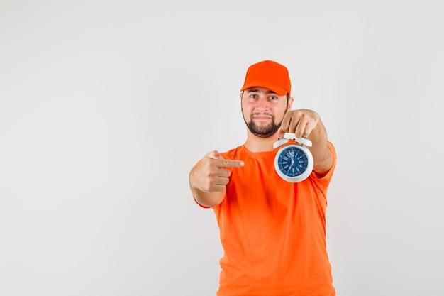 Bezorger wijzend op wekker in oranje t-shirt, pet en zelfverzekerd, vooraanzicht.