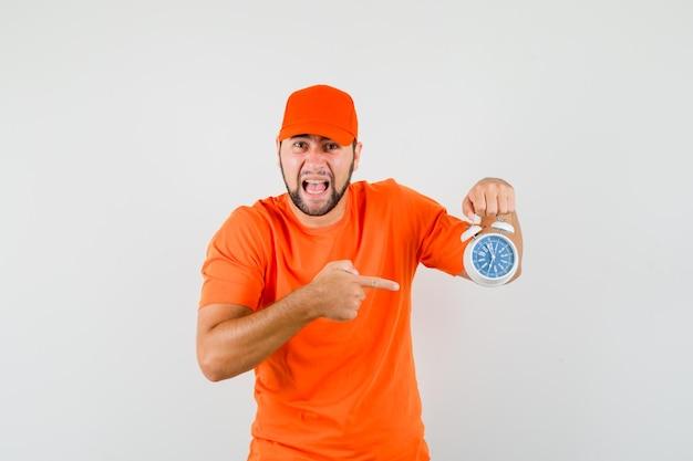 Bezorger wijzend op wekker terwijl hij schreeuwt in oranje t-shirt, pet en geagiteerd kijkt, vooraanzicht.