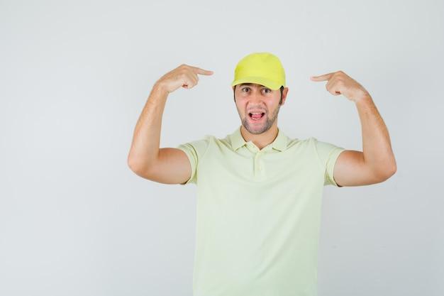 Bezorger wijzend op zijn pet in geel uniform en kijkt zelfverzekerd, vooraanzicht.