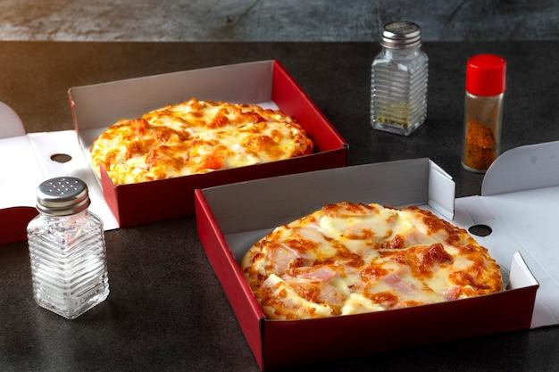 Bezorging pizza spek ham met een hotdog en kaas pizza in de doos kruiden zijn zout