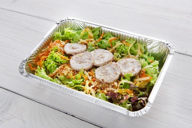 Bezorging van gerechten in het restaurant. haal voedsel weg in foliedozen. groentesalade met konijnenvlees op wit hout