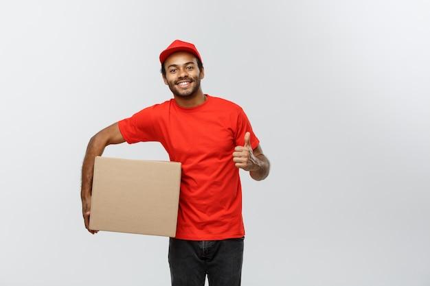 Bezorgingsconcept - portret van gelukkige afro-amerikaanse leveringsman met een doospakket en met een druppel omhoog. geïsoleerd op grijze studio achtergrond. ruimte kopiëren.