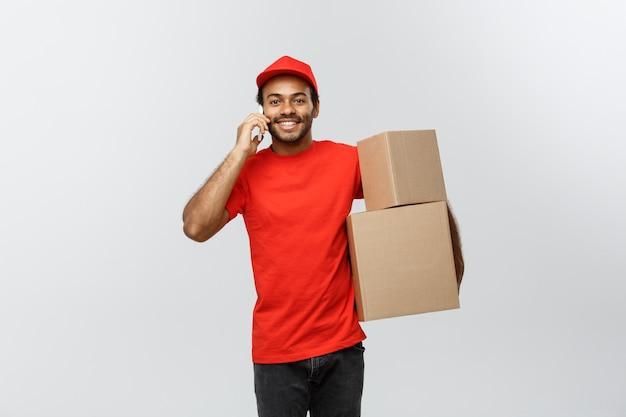 Bezorgingsconcept - portret van knappe afro-amerikaanse leveringsman of koerier met een tablet op u om de bestelling te controleren. geïsoleerd op grijze studio achtergrond. ruimte kopiëren.