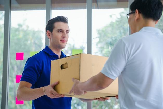 Bezorgingsman die pakketdoos geeft aan ontvanger, man-eigenaar die het pakket van kartondozen van postverzending goedkeurt, online verkoop, elektronische handel, verschepend concept.