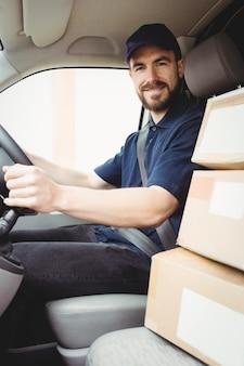 Bezorgingsman die zijn bestelwagen met pakketten op de voorstoel drijven