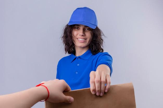 Bezorgingsmeisje in blauw uniform en pet die papieren pakket geven aan een klant die vriendelijk lacht over geïsoleerde witte ruimte