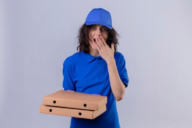 Bezorgingsmeisje in blauw uniform en pet die pizzadozen houden die verbaasd kijken die mond met hand status bedekken