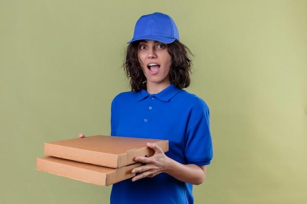 Bezorgingsmeisje in blauw uniform en pet die pizzadozen houden die vreugdevol positief en gelukkig glimlachend vrolijk staan kijken over geïsoleerde groene ruimte