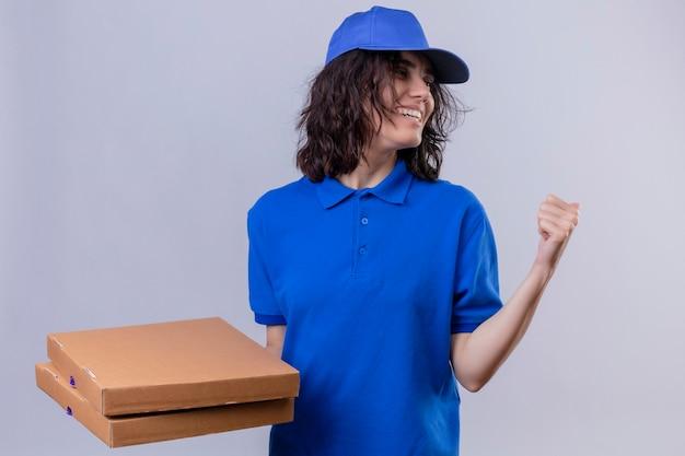 Bezorgingsmeisje in blauw uniform en pet met pizzadozen die naar achteren wijzen met hand en duim die vrolijk staand glimlachen