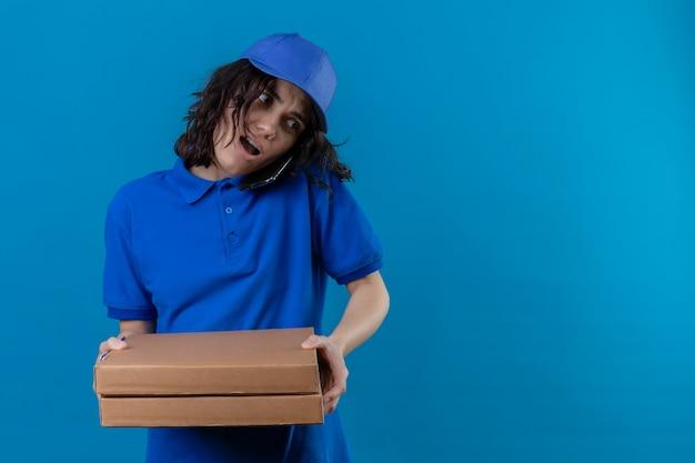 Bezorgingsmeisje in blauw uniform en pet met pizzadozen terwijl ze op de mobiele telefoon praat en kijkt overwerkt staande over geïsoleerde blauwe ruimte