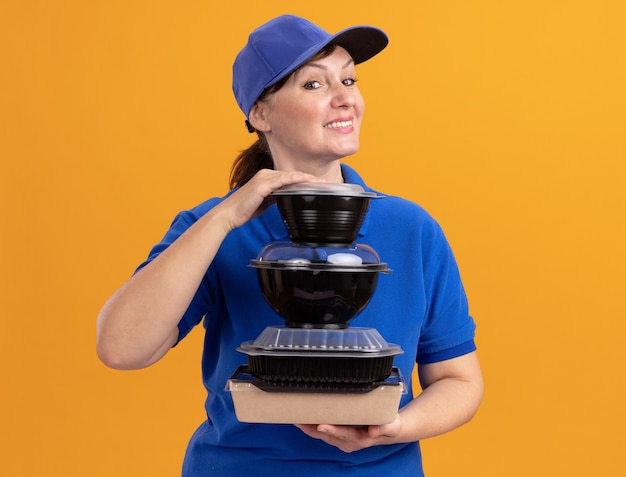 Bezorgingsvrouw van middelbare leeftijd in blauw uniform en glb-holdingsstapel voedselpakketten die voorzijde glimlachend vrolijk statusend over oranje muur bekijken