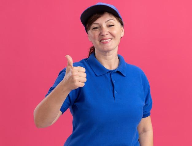Bezorgingsvrouw van middelbare leeftijd in blauw uniform en pet die naar voorzijde glimlachen die vrolijk glimlachend duimen toont die zich over roze muur bevinden