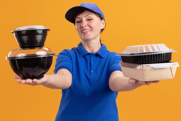 Bezorgingsvrouw van middelbare leeftijd in blauw uniform en pet die voedselpakketten houden die voorzijde het gelukkige en positieve glimlachen bekijken status over oranje muur
