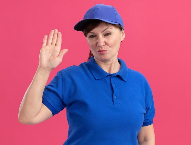 Bezorgingsvrouw van middelbare leeftijd in blauw uniform en pet die voorzijde met zelfverzekerde uitdrukking bekijken die open hand toont die zich over roze muur bevindt