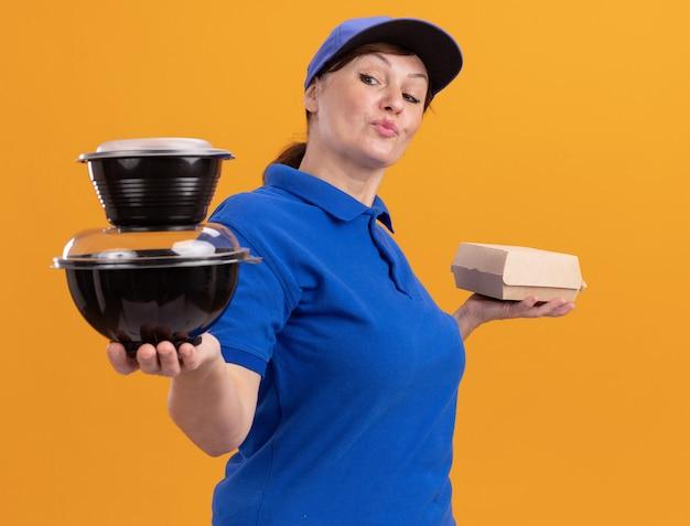 Bezorgingsvrouw van middelbare leeftijd in blauw uniform en pet met voedselpakketten die zelfverzekerd glimlachend staande over oranje muur kijken