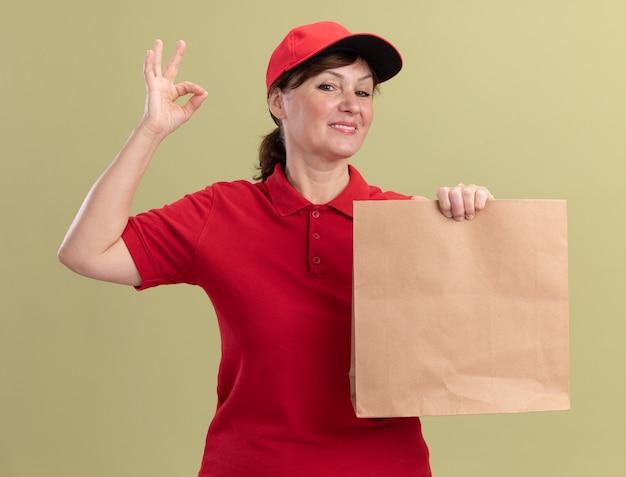 Bezorgingsvrouw van middelbare leeftijd in rood uniform en glb die document pakket houden die voorzijde glimlachen die vrolijk tonen die ok teken tonen dat zich over groene muur bevindt