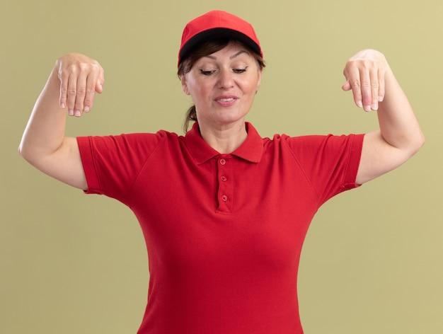 Bezorgingsvrouw van middelbare leeftijd in rood uniform en glb die met handen gebaren kijken die zeker status over groene muur kijken