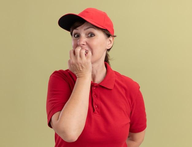 Bezorgingsvrouw van middelbare leeftijd in rood uniform en glb die voorzijde beklemtoonde en zenuwachtige bijtende spijkers bekijken die zich over groene muur bevinden
