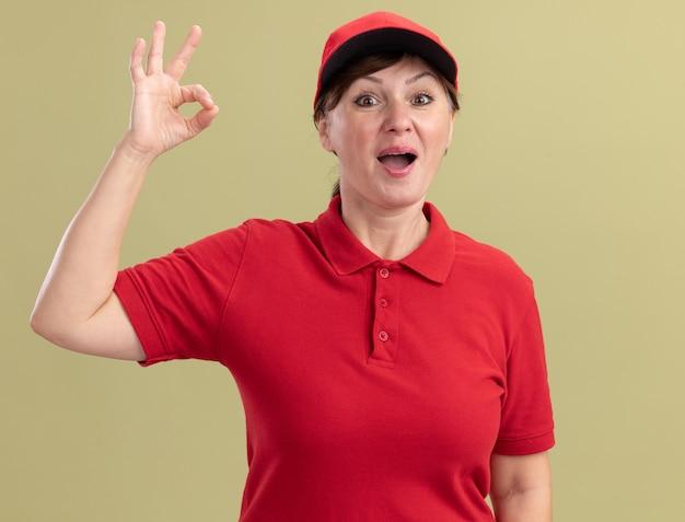 Bezorgingsvrouw van middelbare leeftijd in rood uniform en glb die voorzijde glimlachen die vrolijk glimlachen tonend ok teken tonen dat zich over groene muur bevindt