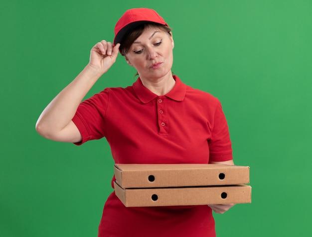 Bezorgingsvrouw van middelbare leeftijd in rood uniform en pet die pizzadozen houden die hen met ernstig gezicht bekijken die zich over groene muur bevinden