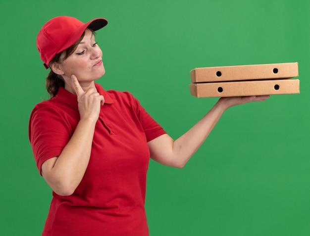 Bezorgingsvrouw van middelbare leeftijd in rood uniform en pet die pizzadozen houden die hen met peinzende uitdrukking op gezicht bekijken die zich over groene muur bevinden