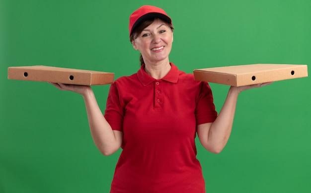 Bezorgingsvrouw van middelbare leeftijd in rood uniform en pet die pizzadozen houden die voorzijde glimlachend met gelukkig gezicht bekijken die zich over groene muur bevinden