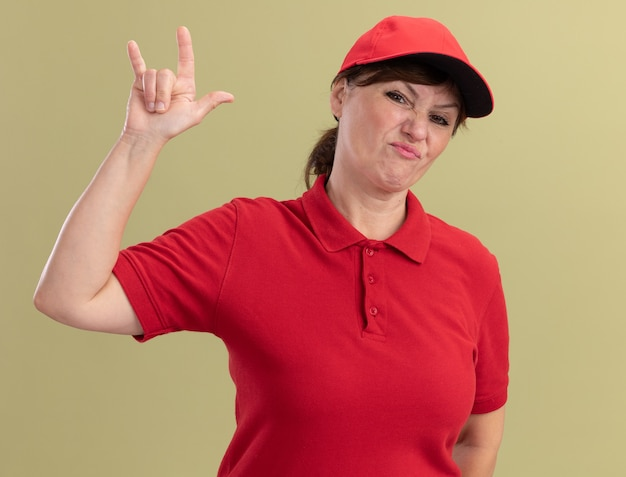Bezorgingsvrouw van middelbare leeftijd in rood uniform en pet die voorzijde bekijken die ontevreden wordt tonend rotssymbool dat zich over groene muur bevindt