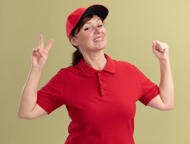 Bezorgingsvrouw van middelbare leeftijd in rood uniform en pet die voorzijde glimlachend met blij gezicht bekijken dat v-teken toont en vuist opheft die zich over groene muur bevindt