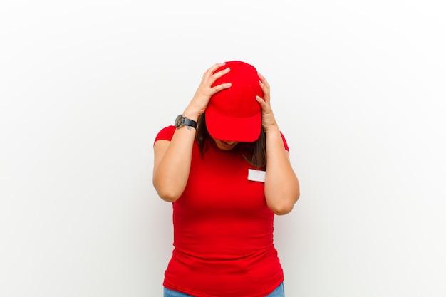 Bezorgingsvrouw voelt zich gestrest en gefrustreerd, heft haar handen op, voelt zich moe, ongelukkig en met migraine tegen wit