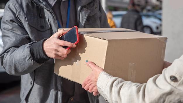 Bezorgkoerier bezorgt pakket aan vrouw, van dichtbij