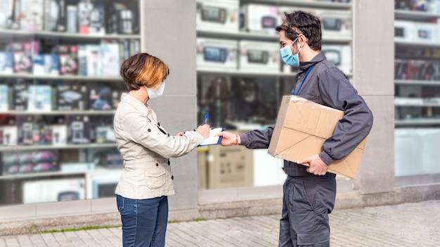 Bezorgkoerier levert doos aan vrouw. de vrouw tekent voor het pakket