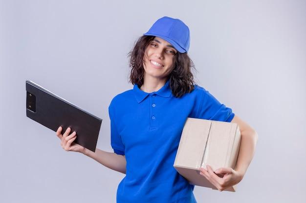 Bezorgmeisje in blauw uniform en pet met doos pakket en klembord glimlachend vriendelijke status