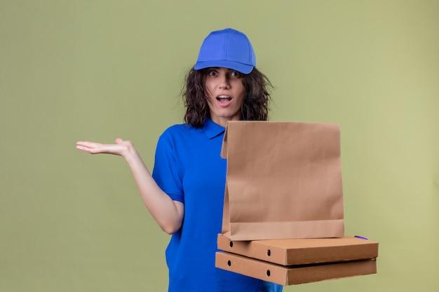 Bezorgmeisje in blauw uniform met pizzadozen en papieren pakket kijkt onzeker en verward, heeft geen antwoord en spreidt palmen die op olijfkleur staan