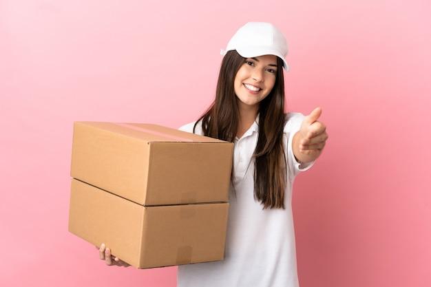 Bezorgmeisje over geïsoleerde roze muur die handen schudt voor het sluiten van een goede deal